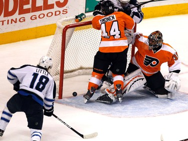 Winnipeg Jets' center Bryan Little (L) watches as his shot slides past the goal near Philadelphia Flyers' goalie Ilya Bryzgalov (R) and Flyers' defenseman Kimmo Timonen (C) during the first period of their NHL ice hockey game in Philadelphia, Pennsylvania, January 31, 2012. REUTERS/Tim Shaffer (UNITED STATES - Tags: SPORT ICE HOCKEY)