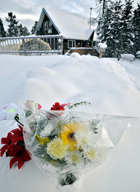 Flowers rest in a snowbank at the scene of five deaths in the Porter Creek area of Whitehorse, Yukon on January 30, 2012. (IAN STEWART/Yukon News)