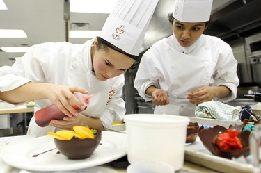 (left to right) Members of the Harry Ainlay culinary team Carol Robillard, 16, and Aashna Thakor, 16, put the finishing touches on their chocolate mousse dessert, during the High School Culinary Challenge at NAIT, Saturday Feb. 4, 2012. Thirteen team's from Edmonton and the surrounding area took part in the competition, which required them to create a three course meal. BLOOM EDMONTON SUN  QMI AGENCY