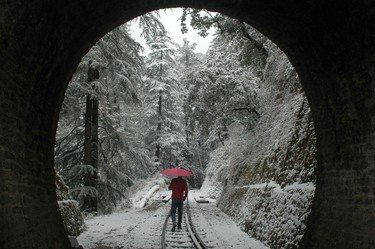 A man walks along a snow covered railway track in Shimla, India's northern state of Himachal Pradesh on February 8, 2012.  AFP PHOTO / STR