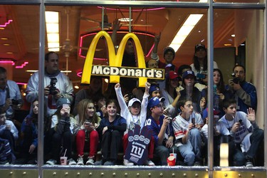 People watch Giants' Victory Parade from a McDonalds' window on February 7, 2012 in New York City. The Giants defeated the New England Patriots 21-17 in Super Bowl XLVI. (Andrew Burton/Getty Images/AFP)