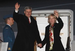 Canada's Prime Minister Stephen Harper and his wife Laureen wave while disembarking their plane after arriving in Beijing February 7, 2012. (REUTERS/Chris Wattie)