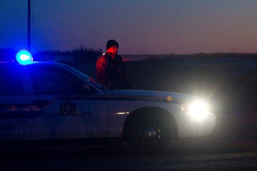 An RCMP car blocks the road at Hwy. 13 and Range Road 121 leading to a house where two RCMP officers were shot and wounded near Killam, Alta., on Tuesday, February 7, 2012. (CODIE MCLACHLAN/QMI AGENCY)