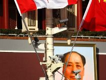 The Canadian and Chinese national flags hang from a pole in front of the giant portrait of former Chinese chairman Mao Zedong at Beijing's Tiananmen Square