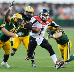 Rod Davis, left, and Greg Peach right, shown here running down Henry Burris in a game against the Stampeders last season, likely won't be in the Eskimos lineup Tuesday morning, barring any last-minute deals. (QMI Agency file)