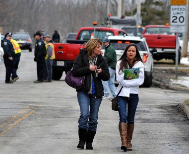 A student walks away from Chardon High School with her mother after a gunman shot one girl and four boys in Chardon, Ohio February 27, 2012.   REUTERS/Ron Kuntz