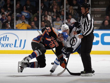 UNIONDALE, NY - APRIL 05: Bryan Little #18 of the Winnipeg Jets out duels Jay Pandolfo #29 of the New York Islanders on the faceoff at the Nassau Veterans Memorial Coliseum on April 5, 2012 in Uniondale, New York. The Islanders defeated the Jets 5-4.   Bruce Bennett/Getty Images/AFP