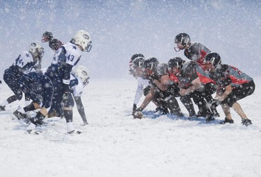 The Airdrie Northern Raiders (right) square off against the Calgary Cowboys on the snow-covered turf at Shouldice Park in Calgary on April 4, 2012. (CHRIS SIMNETT/QMI Agency)