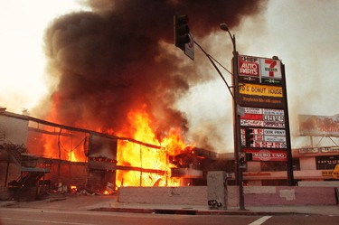 A corner shopping center is fully engulfed in flames as it is left burning during the third day of the Los Angeles Riots in Koreatown, Los Angeles, California in this May 1, 1992, file photo. (REUTERS/Hyungwon Kang/Los Angeles Times/Files)