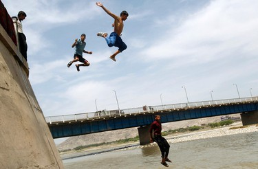 Boys jump into a river to cool themselves in Jalalabad province on May 6, 2012. (REUTERS/Parwiz)