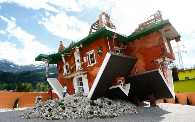 People walk out of a house, which was built upside down by Polish architects Irek Glowacki and Marek Rozanski, in the western Austrian village of Terfens May 5, 2012. The project is meant to serve as a new tourist attraction in the area, and is now open for public viewing. REUTERS/Dominic Ebenbichler