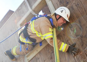 Firefighter Shawn Wilson practises using a hose to climb down from a simulated burning building, during survival training at the Wellington Street station in Sarnia on Thursday. Three provincial instructors took 10 Sarnia firefighters through the training over a five-day course. TYLER KULA/ THE OBSERVER/ QMI AGENCY