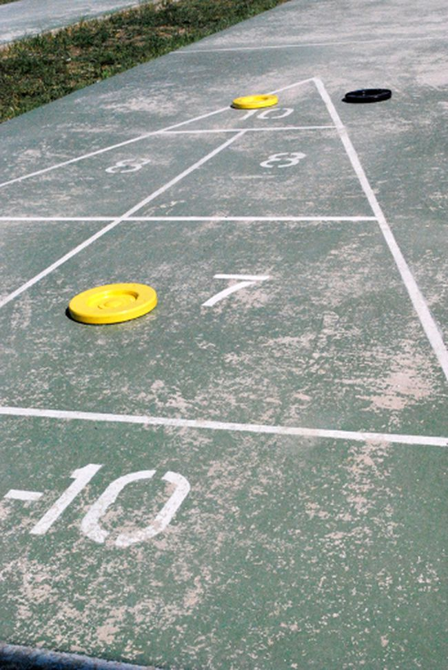 In shuffleboard, players earn points by landing their discs within certain point ranges. Players can knock the discs of others. 