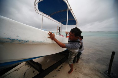 Men push a boat ashore as Hurricane Ernesto approaches the southern part of the Yucatan peninsula, in Mahahual August 7, 2012. REUTERS/Victor Ruiz