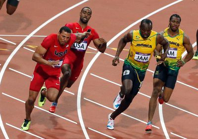 Jamaica's Usain Bolt (2nd R) takes the baton from team mate Yohan Blake as they compete with Ryan Bailey (L) of the U.S., who took the baton from team mate Tyson Gay, in the men's 4x100m relay final at the London 2012 Olympic Games at the Olympic Stadium August 11, 2012. The Jamaican team won gold and set a new world record of 36.84 seconds. REUTERS/Fabrizio Bensch