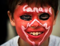 A boy poses for a picture during Canada Day, on the East York Canada Day Parade route in Toronto