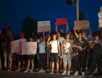 People hold signs during a peaceful demonstration, as communities react to the shooting of Michael Brown in Ferguson
