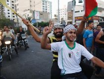 Palestinians celebrate what they said was a victory over Israel, following a ceasefire in Gaza City