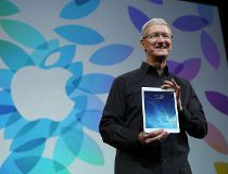 Apple Inc CEO Tim Cook holds up the iPad Air