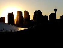 Downtown Calgary skyline at sunset framed by the Scotiabank Saddledome