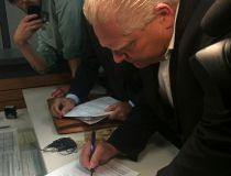 Doug Ford signs the paperwork making his mayoral campaign official. (DON PEAT/Toronto Sun)