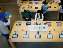 Customers look at Apple iPhone 5c and 5s at an Apple store in Beijing
