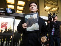 Derek North holds a picture of his cat Pudge outside the Law Courts.