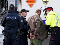 Police officers search a man arrested after approaching police tape near the Canada War Memorial while Prime Minister Stephen Harper paid respect to Cpl. Nathan Cirillo at the Memorial in Ottawa on Oct. 23, 2014. (REUTERS)