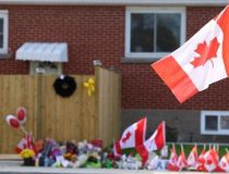 A Canadian flag is affixed to a stop sign near the memorial at the home of slain soldier Cpl. Nathan Cirillo. (ERNEST DOROSZUK/Toronto Sun)