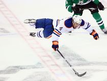 Taylor Hall #4 of the Edmonton Oilers is tripped by Ryan Garbutt