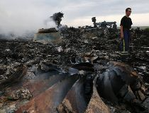 Emergencies Ministry member walks at the site of a Malaysia Airlines Boeing 777 plane crash near the settlement of Grabovo in the Donetsk region