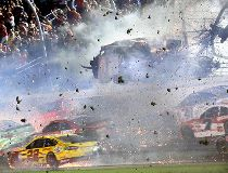Austin Dillon (3) goes airborne and hits the catch fence as he was involved in a multi-car crash on the final lap of the NASCAR Sprint Cup series auto race at Daytona International Speedway, Monday, July 6, 2015, in Daytona Beach, Fla.  (Stephen M. DoweLl