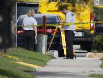Law enforcement officials investigate the scene where an Orange County deputy shot a man who authorities say was stalking a female wrestler outside a World Wrestling Entertainment training facility, Monday, Aug. 31, 2015, in Orlando, Fla. The deputy had n