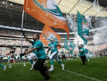 The Miami Dolphins run onto the field for the NFL football game between the New York Jets and the Miami Dolphins and at Wembley stadium in London, Sunday, Oct. 4, 2015. (AP Photo/Tim Ireland)