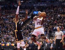 Cleveland Cavaliers' Lebron James, right, looks to pass over Toronto Raptors' DeMarre Carroll during second half NBA basketball action in Toronto on Wednesday, November 25, 2015
