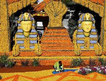 "A worker puts the final touch to a replica of a giant pharaons made with lemons and oranges which shows a scene of the movie ""Cleopatra"" during the Lemon festival in Menton"