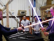 Britain's Prince William, right, and Prince Harry use light sabres
