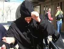 Andrea Giesbrecht tries to hide from the media as she leaves the Law Courts in Winnipeg, Man. Thursday April 21, 2016. Giesbrecht is charged with concealment after the bodies of six infants were found in a storage locker.