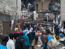 People help survivors retrieve their household items at the site of a building collapse in Nairobi, Kenya
