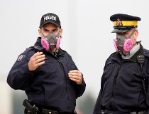 Royal Canadian Mounted Police officers wear masks to protect themselves from smoke from nearby wildfires while directing traffic at a roadblock near Fort McMurray
