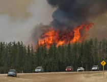 A wildfire burns as evacuees who were stranded north of Fort McMurray, Alberta, Canada head south of Fort McMurray