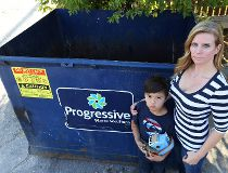 Kristine Kennedy and her son Finnley, 7, pose near a dumpster in the Corydon village area of Winnipeg on Wed., Sept. 14, 2016. Kennedy said was forced to retrieve some toys and other personal items from the dumpster when the person buying her condo entere