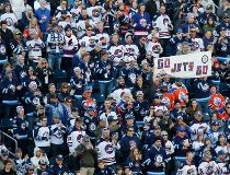 Winnipeg Jets fans hold up a sign during the 2016 Tim Hortons NHL Heritage Classic hockey game on October 23, 2016 at Investors Group Field in Winnipeg, Manitoba, Canada. (Photo by Fred Greenslade /Getty Images)