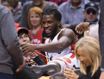 Raptors' DeMarre Carroll checks out a young lady he landed on after launching into the third row during the second half of the Toronto Raptors game against the Atlanta Hawks at the Air Canada Centre. (Stan Behal/Toronto Sun/Postmedia Network)