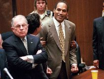 In this Oct. 3, 1995 file photo, O.J. Simpson, center, clenches his fists in victory after the jury said he was not guilty in the murders of his ex-wife Nicole Brown Simpson and her friend Ronald Goldman in a Los Angeles courtroom as attorneys F. Lee Bail