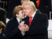 President Donald Trump, right, smiles with his son Barron as they view the 58th Presidential Inauguration parade for President Donald Trump in Washington. Friday, Jan. 20, 2017 (AP Photo/Pablo Martinez Monsivais)