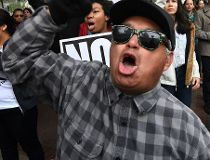 (Paul Horner not pictured) Protesters carry anti-Trump signs during a 'Not My President Day' demonstration outside City Hall in Los Angeles, California, on February 20, 2017. (AFP PHOTO)
