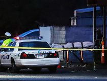A body is removed as police operate at a crime scene outside the Cameo club