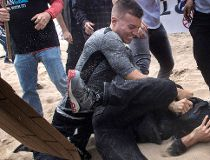 A supporter of President Donald Trump, center, clashes with an anti-Trump protester, bottom center, in Huntington Beach, Calif., on Saturday, March 25, 2017. (Mindy Schauer/The Orange County Register via AP)