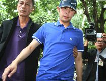 "In this Sept. 3, 2012, file photo, Vorayuth ""Boss"" Yoovidhya, center, whose grandfather co-founded energy drink company Red Bull, is escorted by police in Bangkok, Thailand.(Thai Daily News via AP, File)"